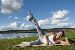 Mature Woman Yoga. A fit and healthy mature woman doing her yoga exercises with one leg up down at a lake Royalty Free Stock Photo