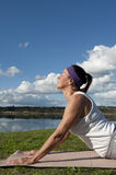Mature Woman Yoga. A fit and healthy mature woman is meditating while doing her yoga exercises at a lake Stock Image