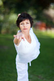 Mature woman yoga. Elegant mature woman doing yoga outdoors in forest Stock Images