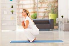 Mature woman yoga. Mature woman doing yoga at home Stock Photo
