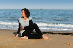 Mature woman yoga on the beach. Mature woman doing Half Lord of the Fishes yoga pose on the beach Royalty Free Stock Photography