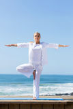 Mature woman yoga beach Royalty Free Stock Images