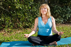 Mature Woman Yoga with Copyspace. Beautiful mature woman doing yoga in a lovely natural setting.  Room for text Stock Photography