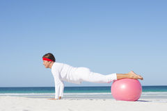 Mature woman yoga exercise beach Stock Images