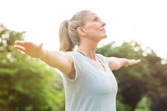 Mature woman yoga exercise. Mature woman doing yoga at park and looking away. Senior blonde woman enjoying nature during a breathing exercise. Portrait of a Stock Photos