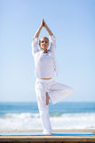 Mature woman yoga. Fit mature woman doing yoga exercise outdoors on beach Royalty Free Stock Photos