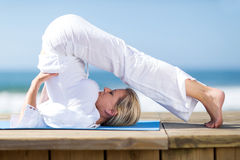 Mature woman yoga. Flexible mature woman yoga by the beach Royalty Free Stock Images