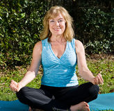 Mature Woman Yoga - Lotus. Fit, beautiful mature woman doing the yoga lotus pose outdoors in a natural setting Royalty Free Stock Photo