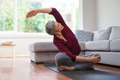 Mature woman in yoga pose. Senior woman exercising while sitting in lotus position. Active mature woman doing stretching exercise in living room at home. Fit stock image