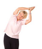Mature woman in yoga position. Mature older lady in yoga position, isolated on white background stock images