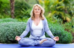 Mature woman in yoga position. Mature woman doing lotus yoga positio outside in the garden Royalty Free Stock Image