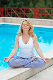 Mature woman in yoga position. Mature woman doing lotus yoga position in front of the pool Stock Image