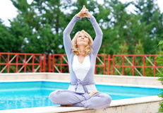 Mature woman in yoga position. Mature woman doing lotus yoga position in front of the pool Stock Photography