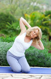 Mature woman in yoga position. Mature woman doing yoga position outside in the garden Royalty Free Stock Photos