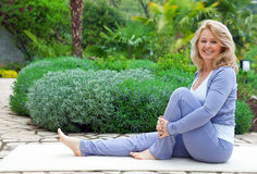 Mature woman in yoga position. Mature woman in relaxation yoga position outside in the garden Royalty Free Stock Photos