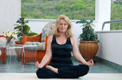 Mature woman in yoga position. Mature woman doing lotus yoga position on her home balcony royalty free stock images