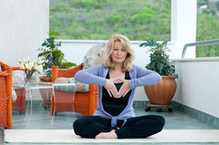 Mature woman in yoga position. Mature woman doing yoga position on her home balcony Royalty Free Stock Photos