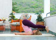 Mature woman in yoga position. Mature woman doing yoga position on her home balcony royalty free stock images