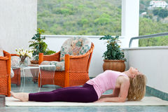 Mature woman in yoga position. Mature woman in relaxation yoga position on her balcony floor royalty free stock image