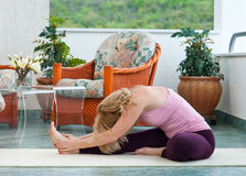 Mature woman in yoga position. Mature woman in relaxation stretching position on her balcony floor royalty free stock photos