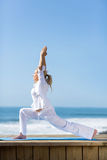 Mature woman yoga. Side view of fit mature woman yoga pose on beach Stock Photography