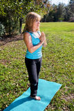 Mature Woman Yoga - Trees. Beautiful mature woman doing the tree pose in yoga out among the trees in nature Royalty Free Stock Photos