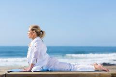 Mature woman yoga. Mature woman upward dog yoga position on beach Royalty Free Stock Image