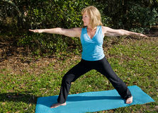 Mature Woman Yoga - Warrior Asana Stock Photos
