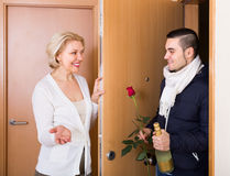 Mature woman and young guy at doorway Royalty Free Stock Photos
