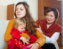 Mature woman and young mother with crying  baby after quarrel Royalty Free Stock Images