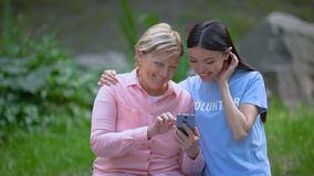 Mature woman and young volunteer looking smartphone photos together, assistance. Stock footage stock footage