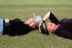 Mature women. Laughing mature woman wearing cowboy hats and lying down in the grass Royalty Free Stock Images