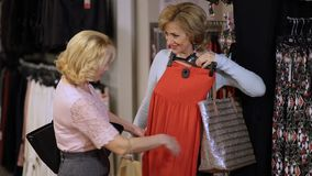 Mature women choosing dress in clothing store stock footage