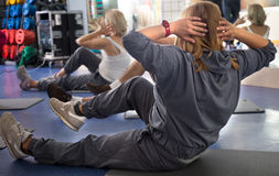 Mature women are engaged on mat in gym. Active mature women are engaged on mat in gym Stock Images