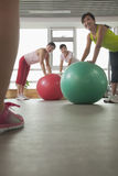 Mature women exercising with fitness ball and looking at the trainer Royalty Free Stock Image