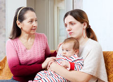 Woman gives solace to sad adult daughter Stock Image