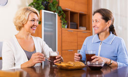 Mature women having tea break. Happy mature women having tea break at office. Focus on blonde woman Royalty Free Stock Image