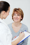 Mature woman with her young female doctor Stock Photos
