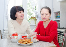 Mature women  at   kitchen table with   cup of tea. Royalty Free Stock Photo