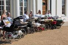 Mature women lined up with collection of vintage prams Royalty Free Stock Photography