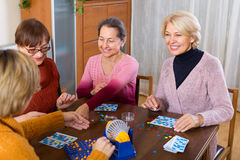 Mature women with table game. Happy smiling female pensioners having fun with table game indoor Royalty Free Stock Photo