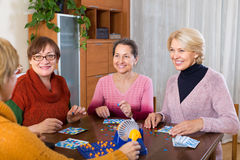 Mature women with table game. Positive mature women having fun with table game indoor Royalty Free Stock Photo