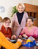 Mature women with table game. Positive senior female friends having fun with table game indoor Royalty Free Stock Photo
