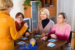 Mature women with table game. Smiling mature women having fun with table game indoor Royalty Free Stock Photography