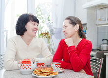 Mature women talking at   kitchen table Royalty Free Stock Photo