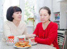 Mature women talking at   kitchen table Royalty Free Stock Image