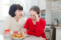 Mature women talking   in   kitchen. Royalty Free Stock Photo