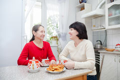 Mature women talking in kitchen Royalty Free Stock Photos