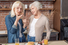 Mature women tasting waffles with jam in kitchen Royalty Free Stock Images
