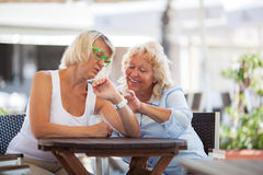 Mature women using smart watch in street cafe Royalty Free Stock Photos